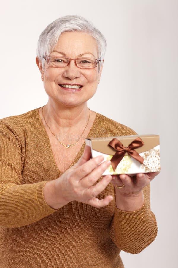 Пожилая дама держа малый присутствующий усмехаться коробки стоковое фото rf