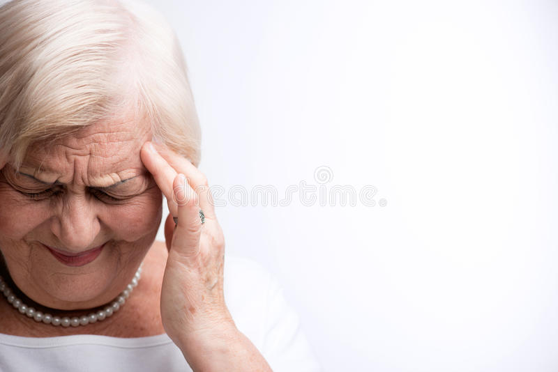 Пожилая дама касаясь ее голове с пальцами стоковые изображения
