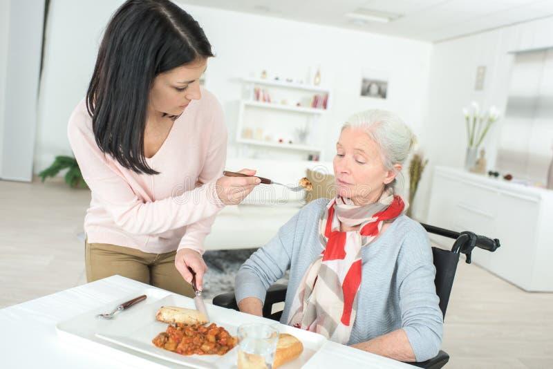 Пожилая дама на кресло-коляске и медсестре стоковое фото