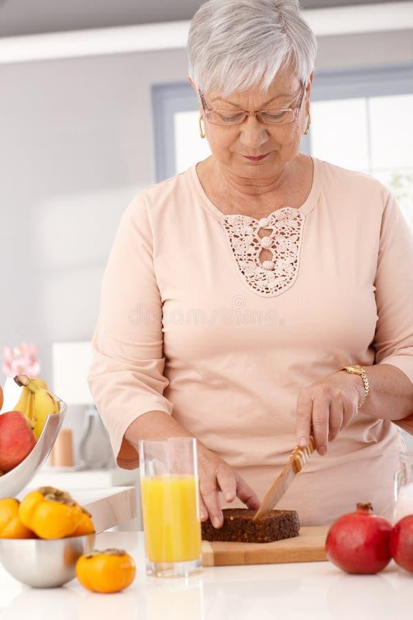 Пожилая дама отрезая здоровый хлеб стоковое фото rf