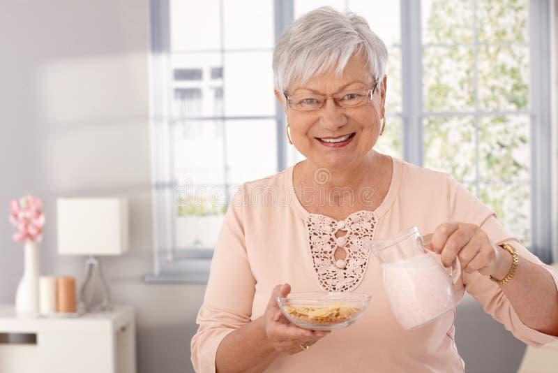 Пожилая дама подготавливая хлопья для завтрака стоковое изображение rf