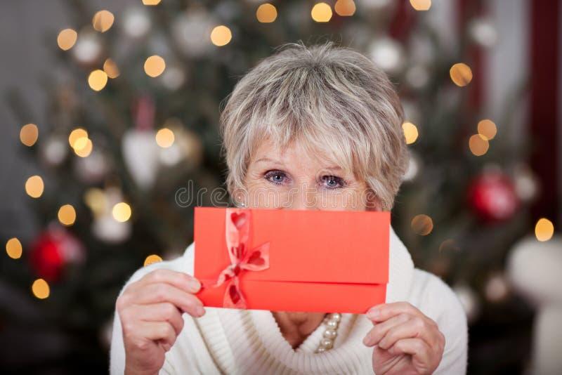 Пожилая дама с красным подарочным сертификатом стоковые изображения rf