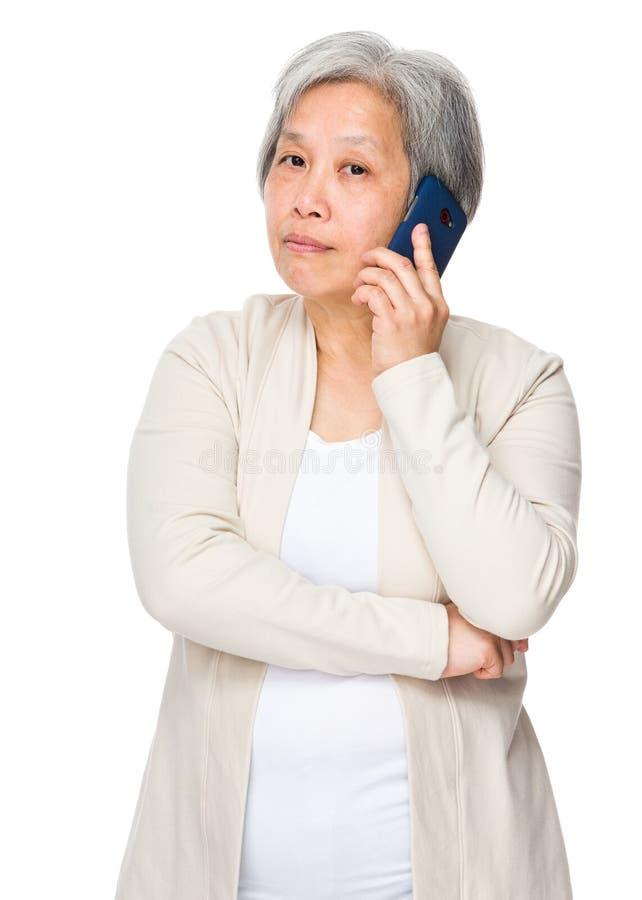 Пожилая беседа женщины к умному телефону стоковое изображение rf