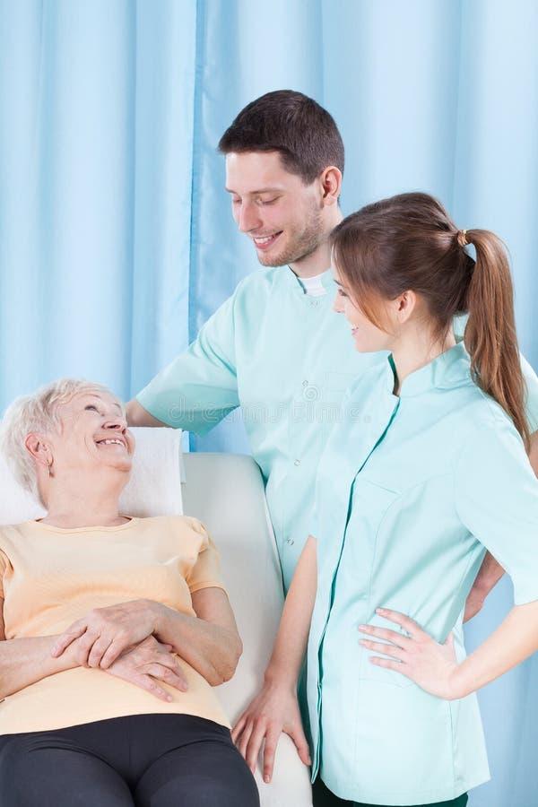 Пожилая женщина говоря к докторам стоковое изображение