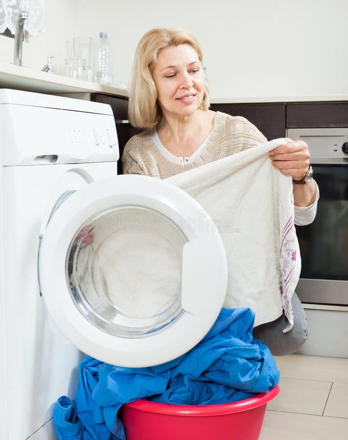 Пожилая женщина делая прачечную с стиральной машиной стоковые изображения rf