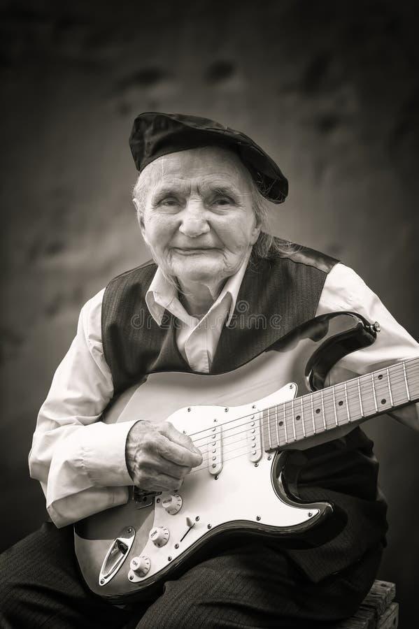 Пожилая женщина играя гитару стоковое изображение rf