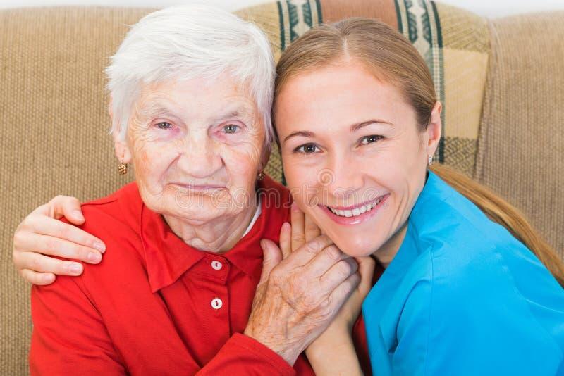 Пожилая женщина и молодой человек осуществляющий уход стоковые изображения rf