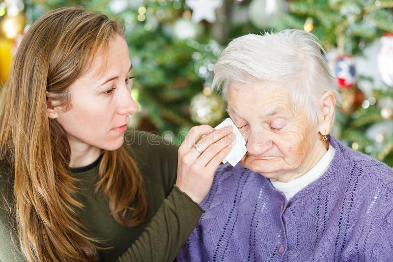 Пожилая женщина и молодой человек осуществляющий уход стоковое изображение