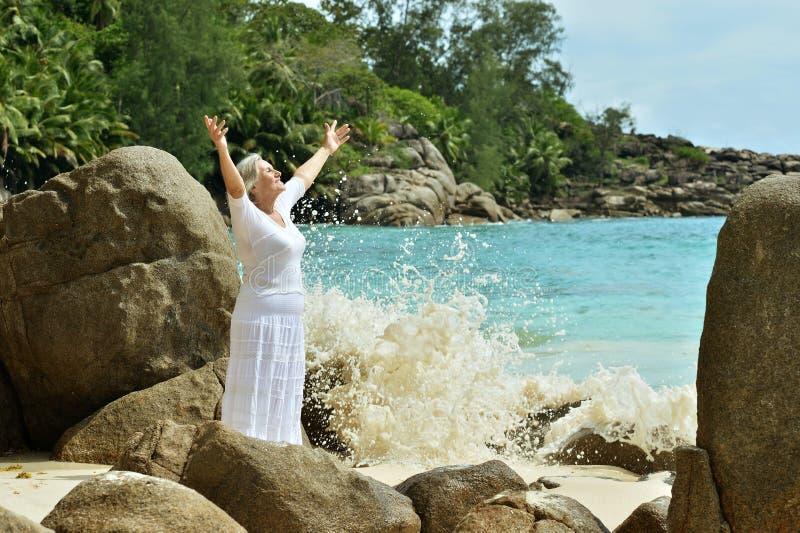 Пожилая женщина на пляже моря стоковые фото
