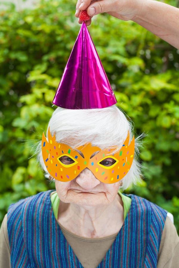 Пожилая женщина нося красочный праздновать маски & шляпы стоковые фото