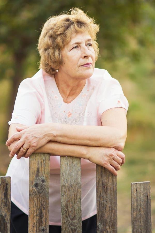 Пожилая женщина около калитки к саду стоковые фотографии rf