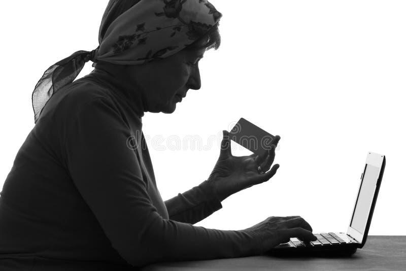 Пожилая женщина оплачивает с карточкой банка на интернете стоковые изображения