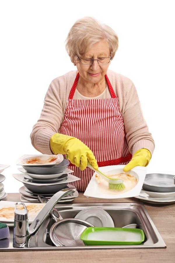 Пожилая женщина очищая блюда с щеткой стоковое изображение rf
