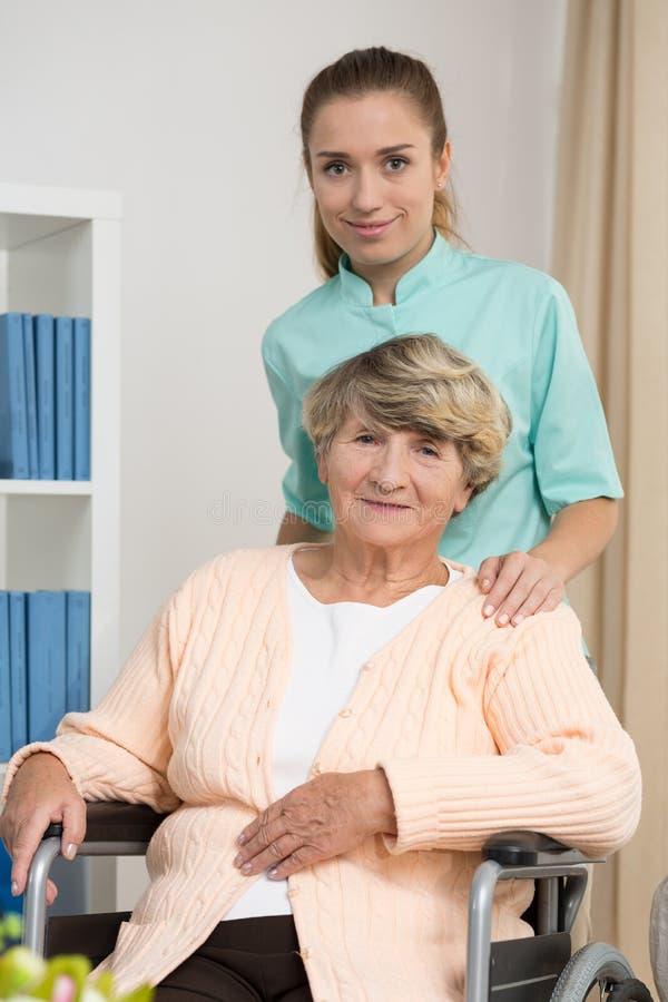 Пожилая женщина сидя на кресло-коляске стоковая фотография rf
