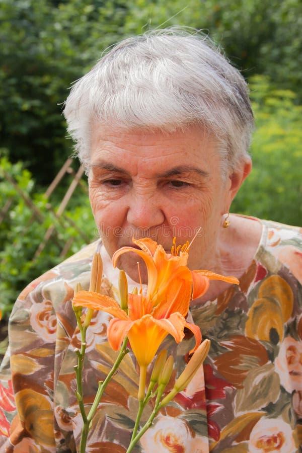 Пожилая женщина стоит около ярких оранжевых цветков стоковая фотография rf