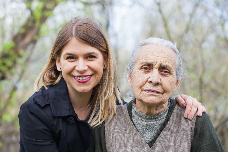 Пожилая женщина с ее человеком осуществляющим уход внешним стоковое фото rf