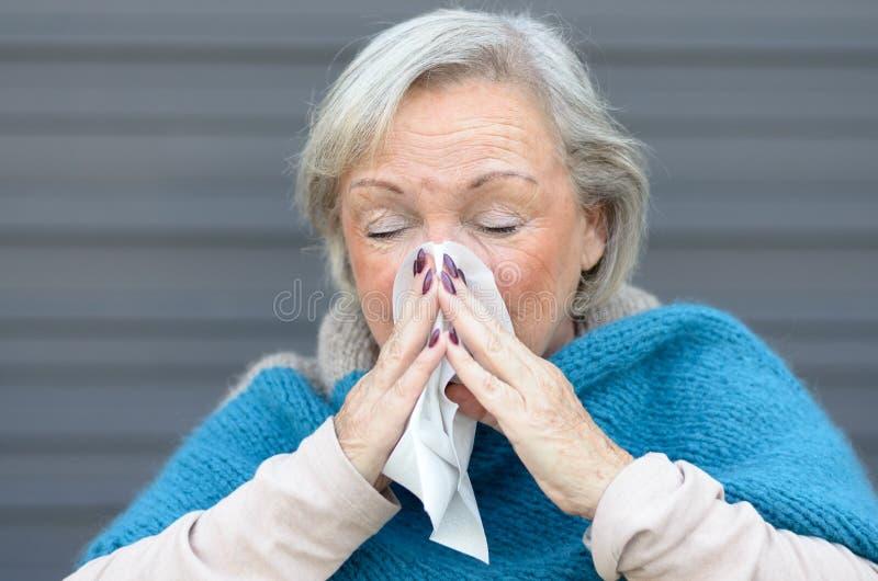 Пожилая женщина с сезонной инфлуензой стоковое изображение