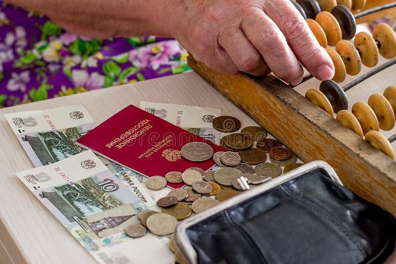 Пожилая кавказская женщина подсчитывая деньги стоковые фото