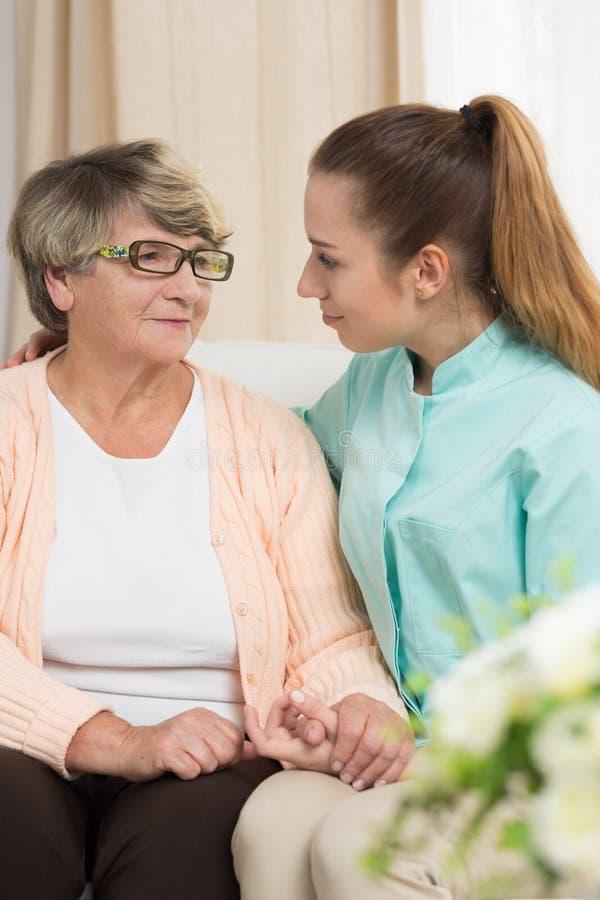 Пожилое женское усаживание около медсестры стоковая фотография