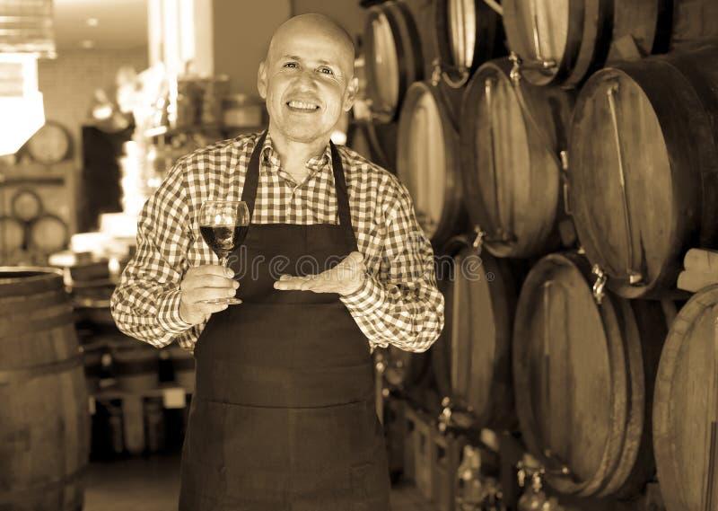Пожилой мужской создатель вина принимая вино от древесины стоковое изображение