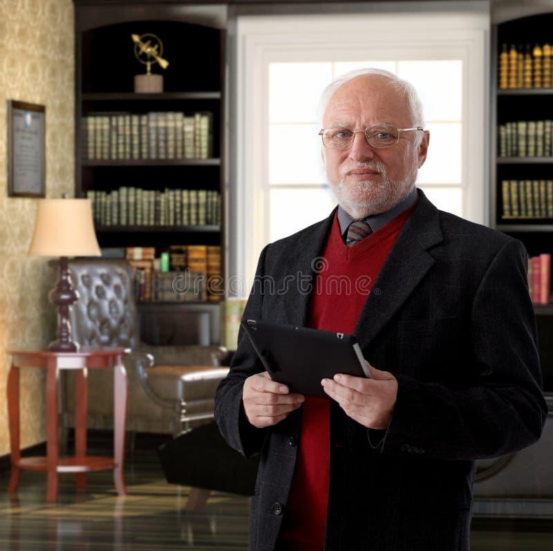 Пожилой профессор на исследовании держа планшет стоковое фото rf