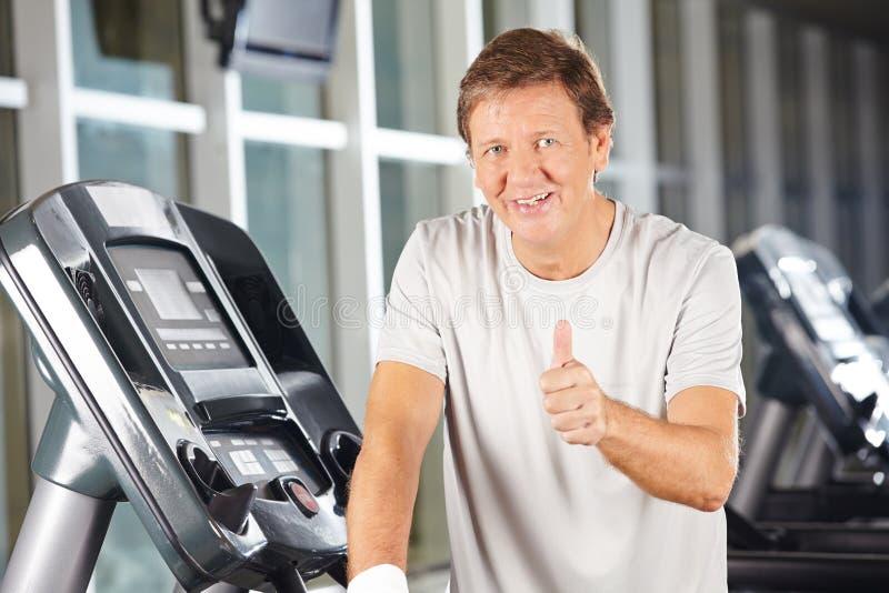 Пожилой человек держа большие пальцы руки вверх в фитнес-центре стоковая фотография