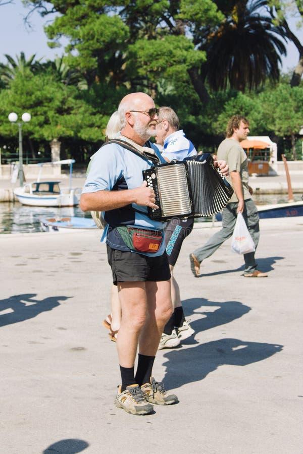 Пожилой человек играя аккордеон снаружи на портовом районе острова стоковые изображения rf