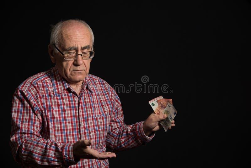 Пожилой человек с деньгами стоковое изображение rf