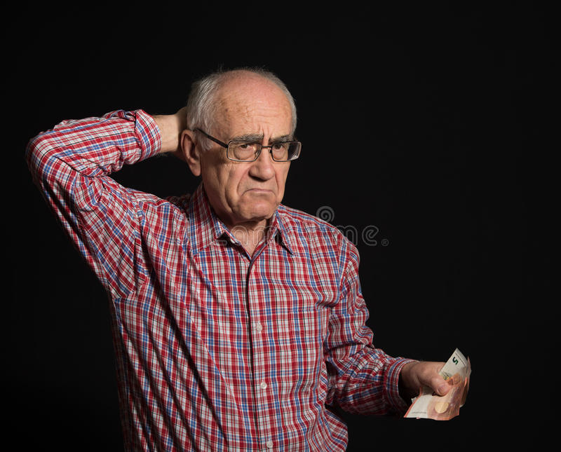 Пожилой человек с деньгами стоковые изображения