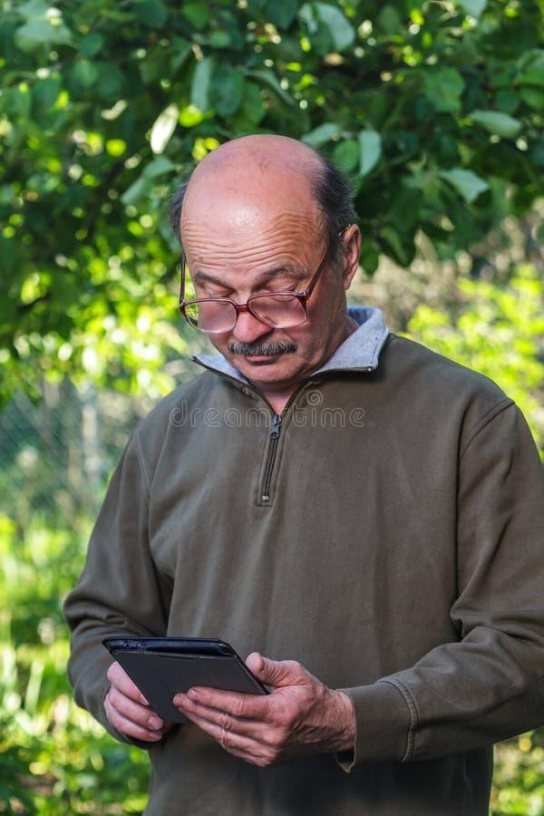 Пожилой человек с лысой головой, усик и стекла учат общаться с таблеткой стоковое фото