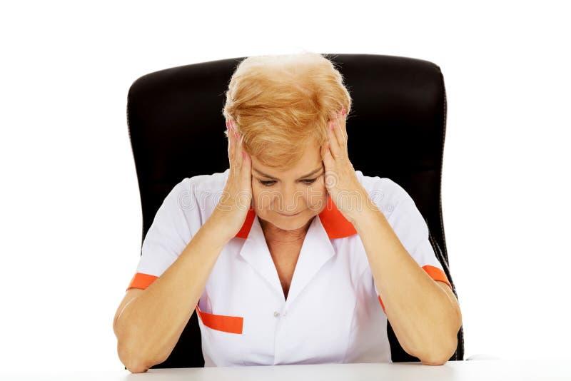 Пожилые женские доктор или медсестра сидя за столом с головной болью стоковое изображение rf