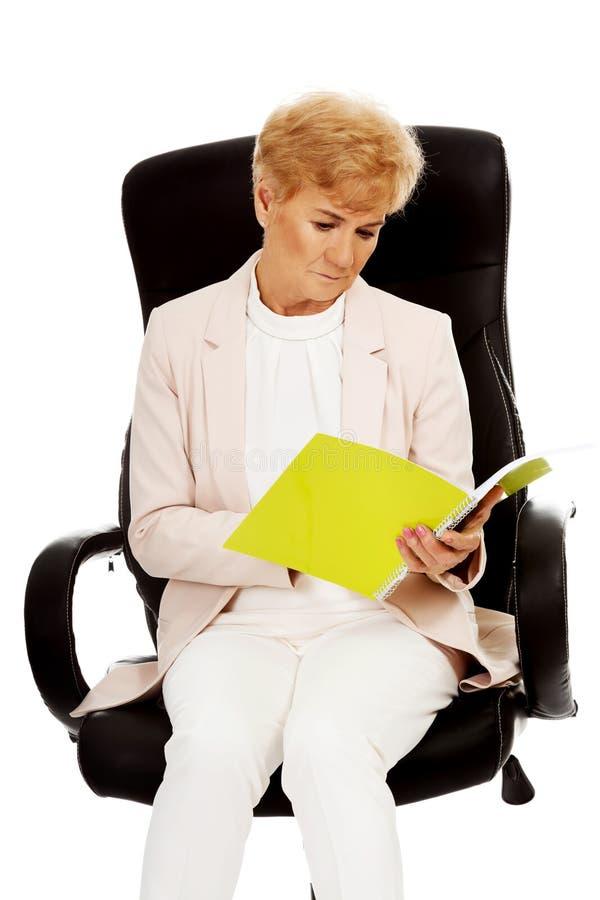 Пожилые задумчивые сфокусированные примечания чтения бизнес-леди стоковые изображения rf