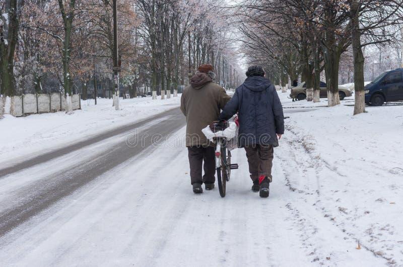 Пожилые пары идя на улицу зимы свертывая старый велосипед нагрузили с сумками в городе Днепр, Украине стоковые изображения