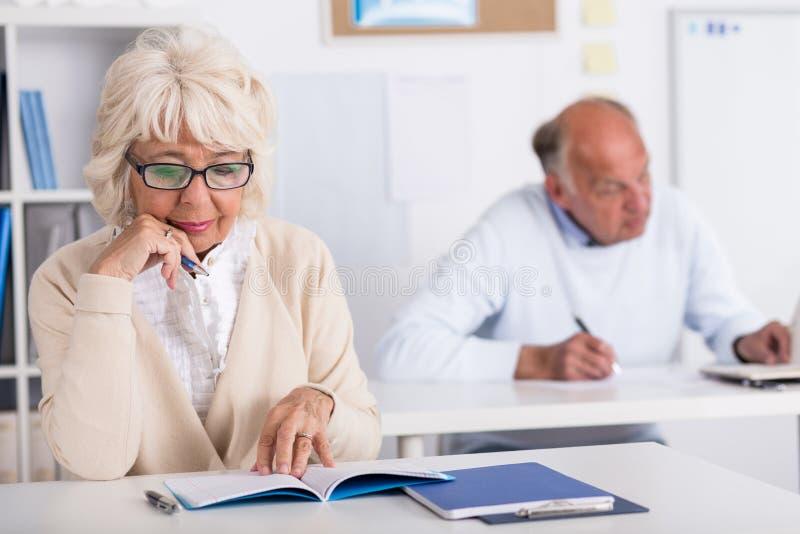 Пожилые студенты работая в классе стоковое фото rf