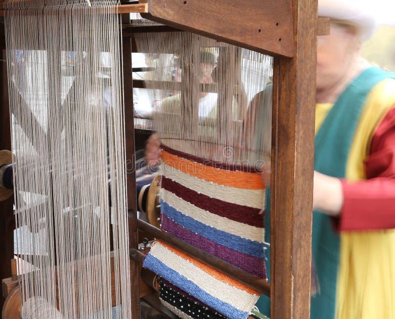 Пожилые ткачи с тенью опытного человека во время соткать  стоковое изображение