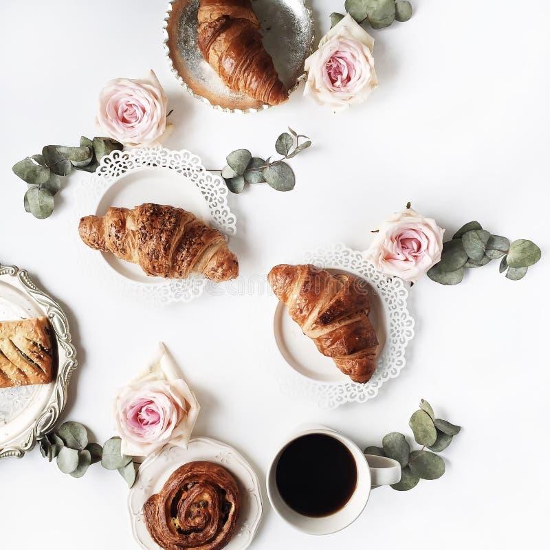 Позавтракайте с круассанами, цветком розы пинка, лепестками, винтажными плитами и составом черного кофе стоковые изображения rf