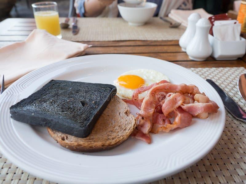 Позавтракайте с питательным имейте уголь, здравицу, бекон и яичко хлеба на белой плите апельсиновый сок, соль и перец на предпосы стоковое фото rf