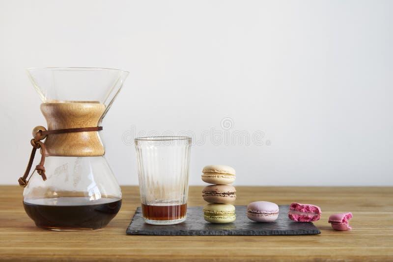 Позавтракайте с свежим кофе в Chemex, сладостных macarons на деревянном столе Красивое ` s женщины вручает лить от стеклянного ша стоковое изображение rf