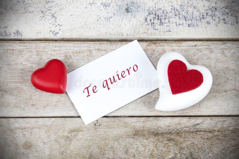 Поздравительная открытка Валентайн на деревянном столе с текстом написанным в испанском quiero Te, которое значит я тебя люблю стоковые изображения