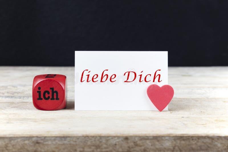 Поздравительная открытка Валентайн на деревянном столе с liebe Dich Ich текста, написанным в немецком, который значит я тебя любл стоковое изображение