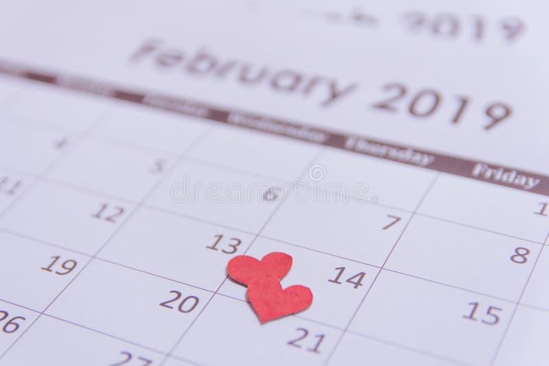 Поздравительная открытка дня Святого Валентина Красная бумага сердец на странице 14-ое февраля календаря с космосом экземпляра стоковое фото rf