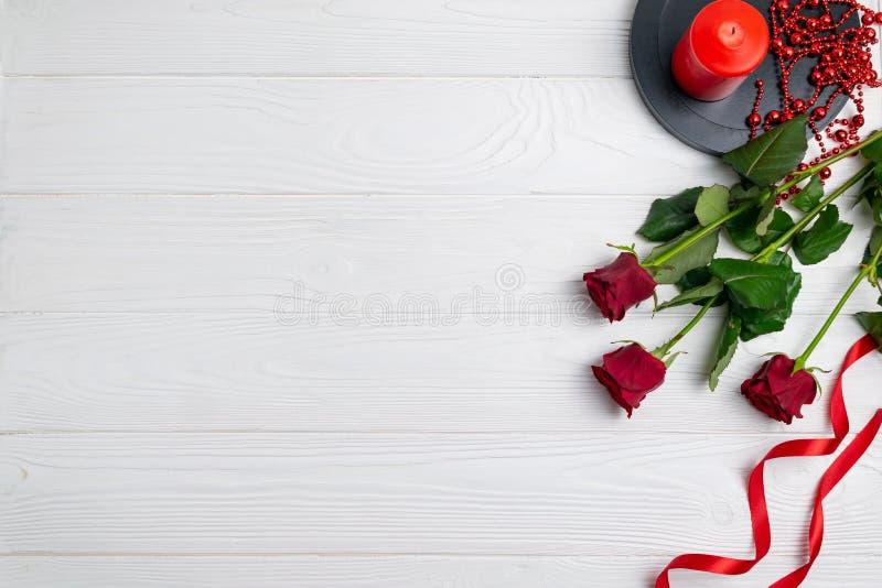 Поздравительная открытка или состав предпосылки с красными розами и свечой с космосом для текста стоковое изображение