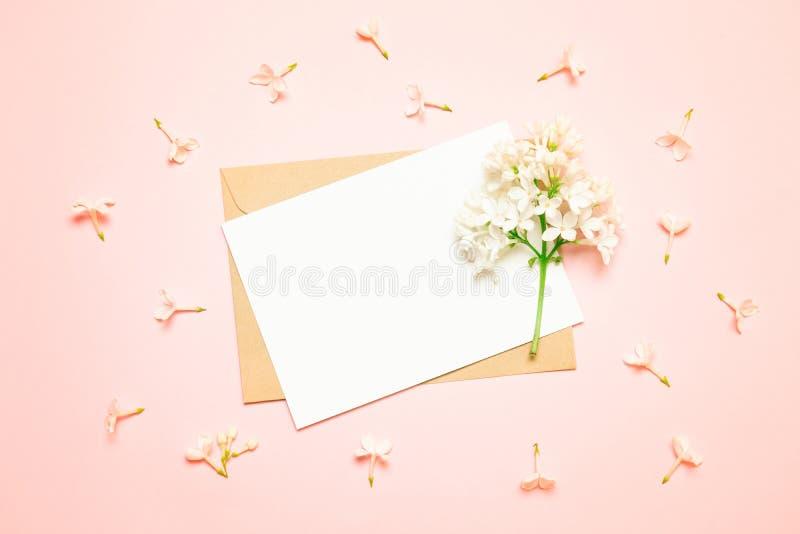 Поздравительная открытка и конверт модель-макета белые с ветвями сирени на светлой предпосылке стоковое изображение rf