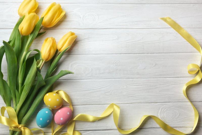 Поздравительная открытка пасхи с букетом цветков тюльпана и пасхальными яйцами Взгляд сверху над деревянным столом с космосом для стоковые изображения rf
