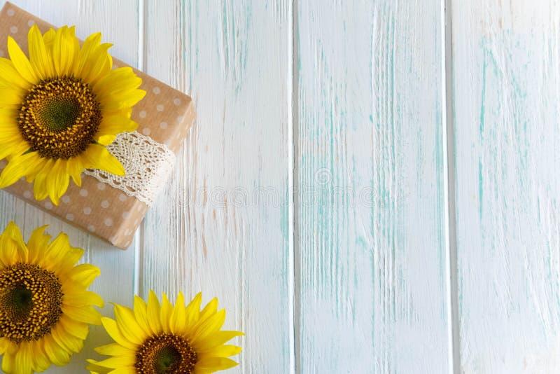Поздравительная открытка с цветками солнцецвета и коробки с подарком на деревянной предпосылке Знамя осени с подводн-солнцецветам стоковая фотография rf
