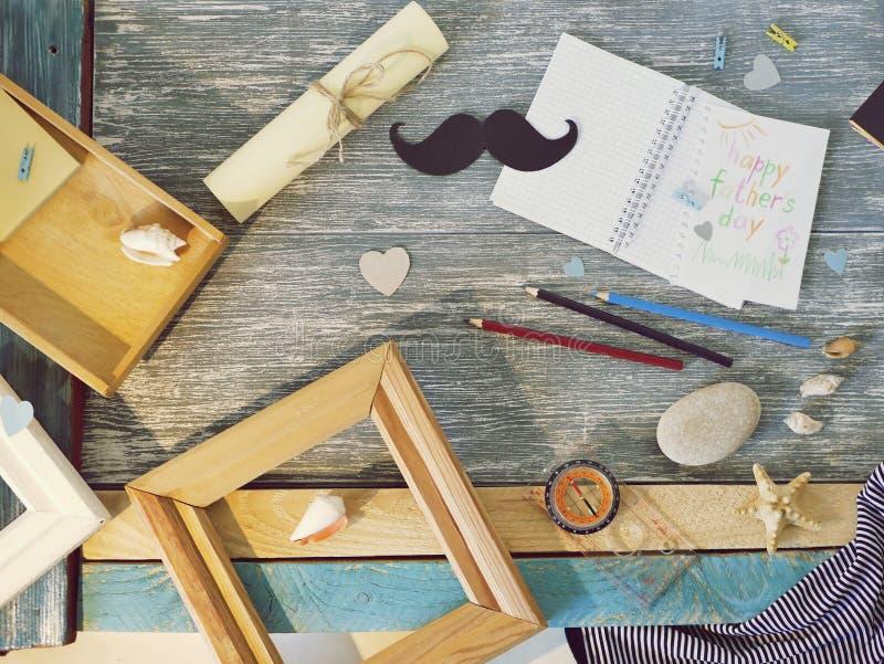 Поздравления на День отца, блокнот, компас, усик бумаги, морское оформление на деревянном столе стоковое изображение rf