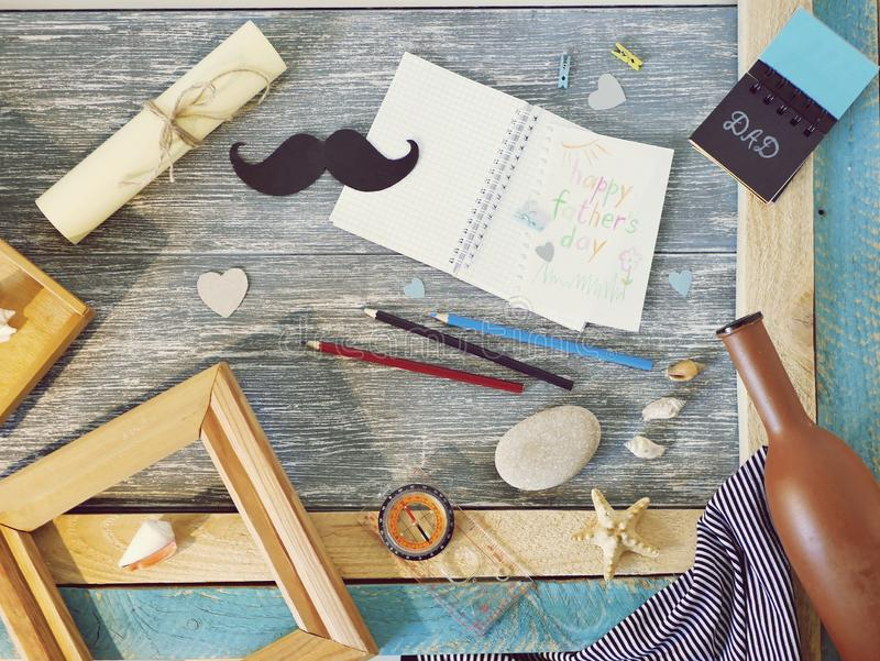 Поздравления на День отца, блокнот, компас, усик бумаги, морское оформление на деревянном столе стоковое фото rf