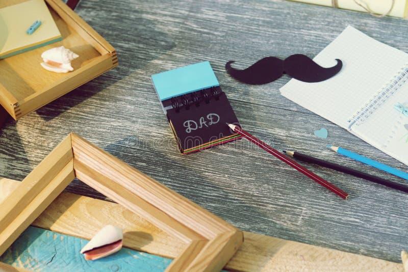 Поздравления на День отца, блокнот, компас, усик бумаги, морское оформление на деревянном столе стоковое изображение