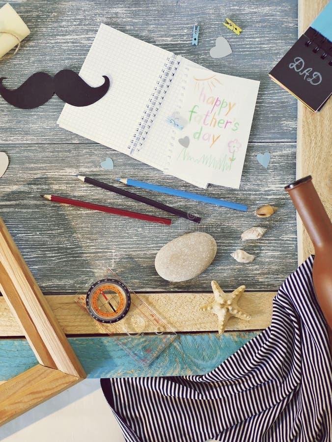 Поздравления на День отца, блокнот, компас, усик бумаги, морское оформление на деревянном столе стоковые фото