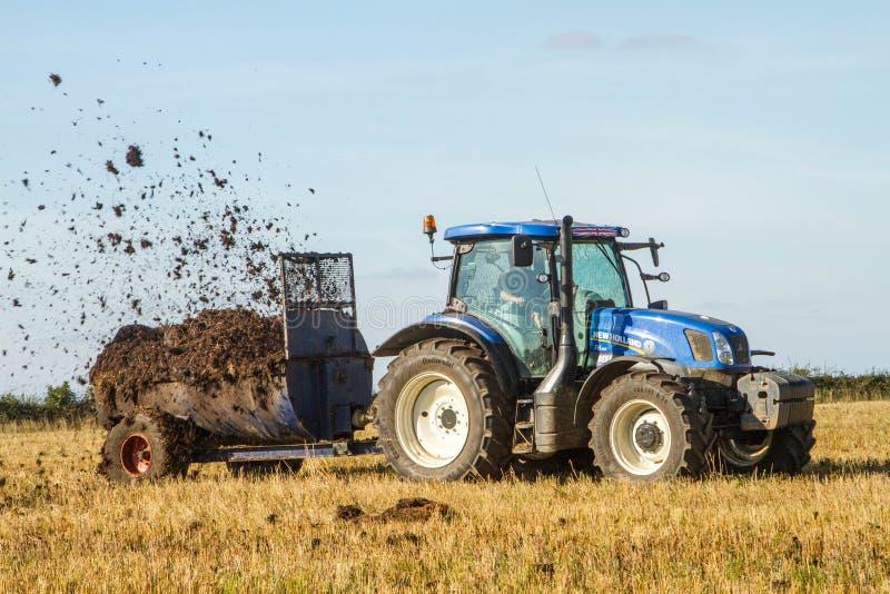 Позем современного нового трактора трактора Голландии распространяя на полях стоковое фото